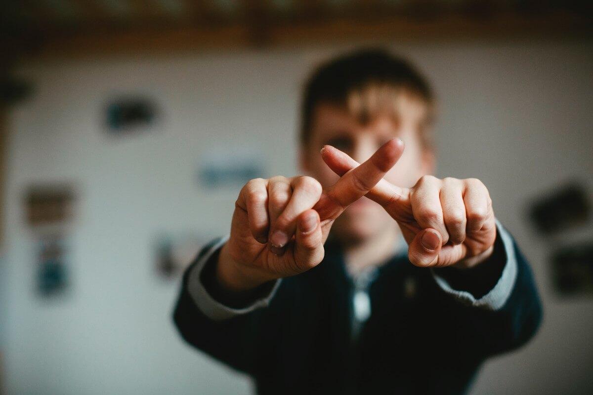 指でバツをつくる男の子